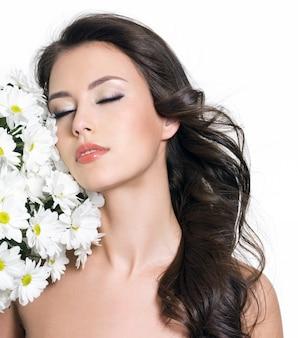 目を閉じて白い花を持つ美しい官能的な若い女性-白い背景