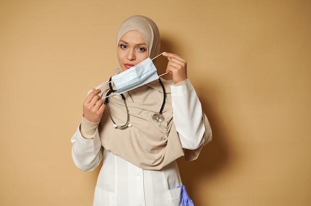 ベージュの表面eithコピースペースに立っている医療マスクを身に着けている美しい穏やかなイスラム教徒の医師
