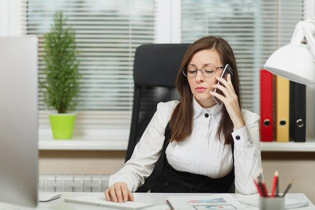 Bella donna d'affari seria in giacca e occhiali seduta alla scrivania, lavorando al computer contemporaneo con documenti in ufficio leggero, parlando al telefono cellulare risolvendo problemi, guardando da parte