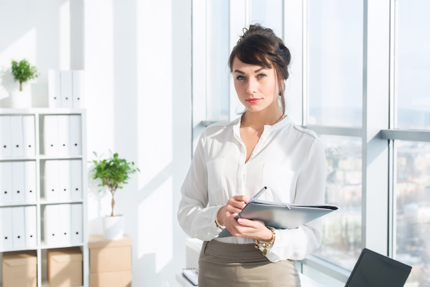 Beautiful, serious consultant wearing glasses and a formal office suit, holding her work stationary,