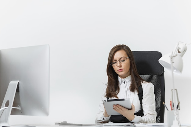 정장을 입고 책상에 앉아 안경을 쓰고 밝은 사무실에서 문서와 태블릿을 갖춘 현대적인 모니터로 컴퓨터에서 일하는 아름다운 진지한 갈색 머리 비즈니스 여성