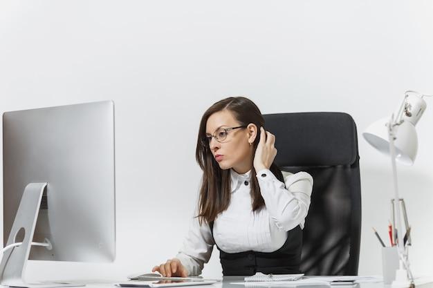 La bella donna d'affari dai capelli castani seria e assorta in giacca e occhiali seduta alla scrivania, che lavora al computer con un monitor moderno con documenti in ufficio leggero,