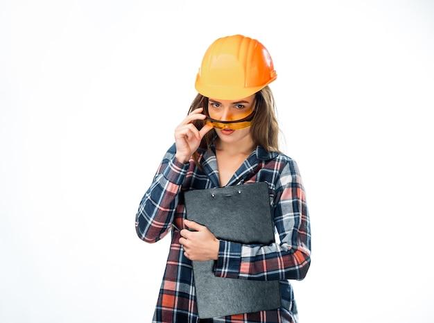 白で隔離のビジネスプランを書く美しい真面目な女性建築家。ヘルメットとメガネの魅力的な労働者は黒いフォルダーを保持します