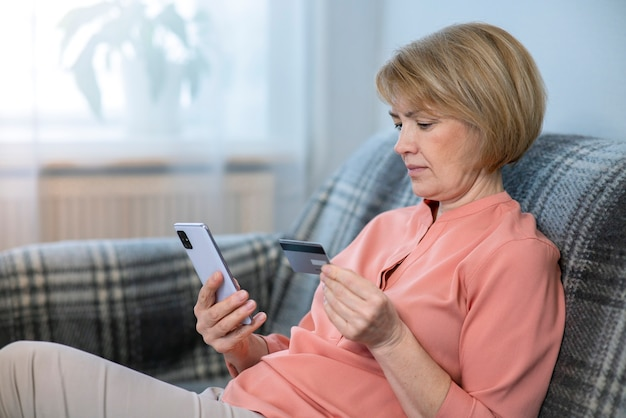 Beautiful serious focused elderly senior woman at home with mobile phone, smartphone, buying, using, holding in hand credit bank card for internet shopping. online payment concept.