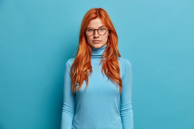 아름답고 진지한 빨간 머리 밀레 니얼 여성은 차분한 자신감 표현으로 직접 외모가 캐주얼 한 옷을 입은 광학 안경을 착용하는 것을주의 깊게 듣는다.