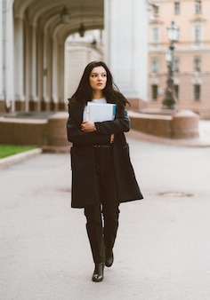 Beautiful serious smart girl brunette student holding notebooks and textbooks, goes walking