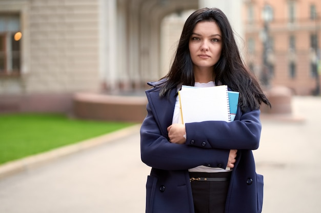 Beautiful serious smart girl brunette student holding notebooks and textbooks, stands at university