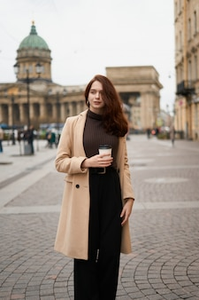 Beautiful serious stylish fashionable smart girl holding cup of coffee in hands goes walking down street