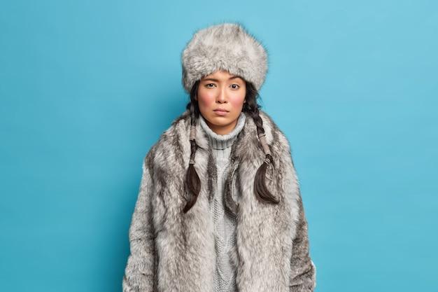正面に焦点を当てた美しい真面目な女性は、青い壁の上に寒い天候のポーズのための冬の帽子のコートのドレスを着ています。アウターウェアのクリスマスの女の子