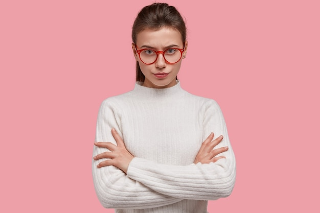 Beautiful serious woman keeps arms folded, looks directly at camera, has dark hair combed in pony tail, looks self assured, wears white clothes