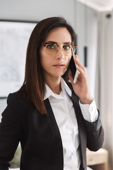 Beautiful serious young business woman in formal wear clothes indoors at home talking by mobile phone.