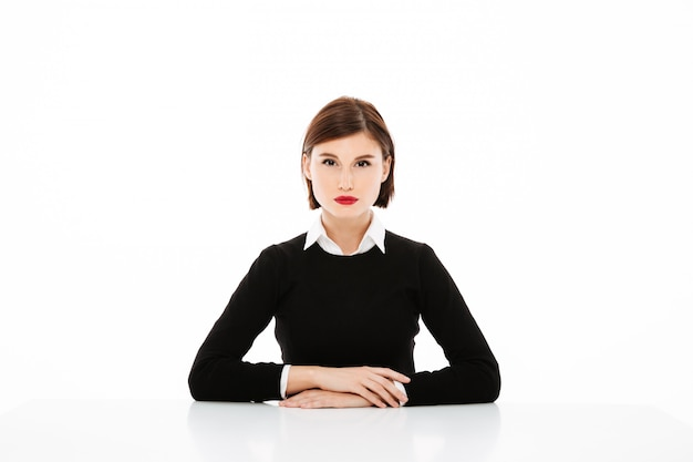Beautiful serious young business woman sitting at the table, job interview concept