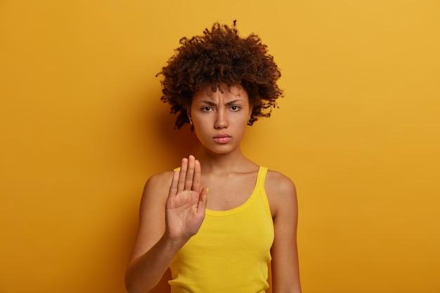 Красивая серьезная молодая женщина требует удержать и делает запрет