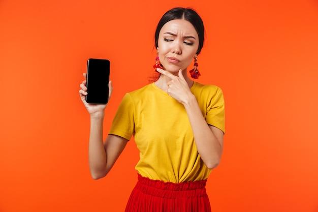 Красивая серьезная молодая женщина позирует изолированной над оранжевой стеной, показывающей дисплей мобильного телефона.