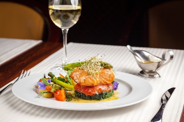 Beautiful serving dishes in the restaurant, red fish salmon with vegetables on a white plate in a restaurant on a black background with white wine stokanom