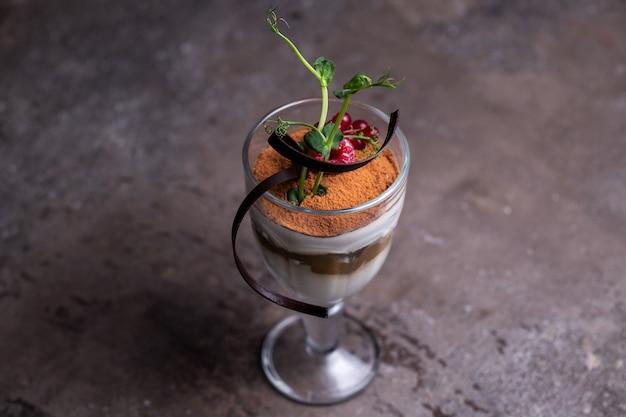 Красивая сервировка блюда десерт тирамису в бокале с ягодами.