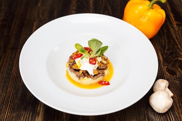 Красивая сервировка белой тарелки горячего бефстроганова или бефстроганова с картофелем, чили и шпинатом.