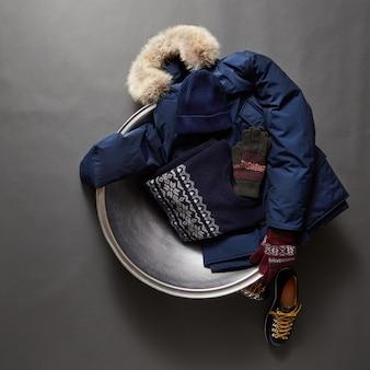 Красивый комплект зимней мужской одежды на черной поверхности