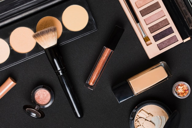 Beautiful set of professional makeup cosmetics on dark table