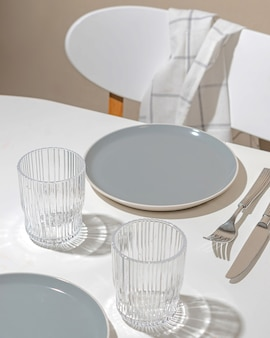 Beautiful setting - empty plates and glasses on the table. hard sunlight light