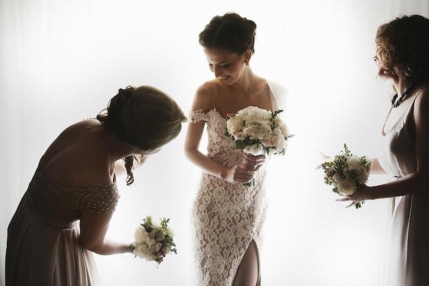 Красивая сексуальная брюнетка невесты в белом платье с подружками возле окна