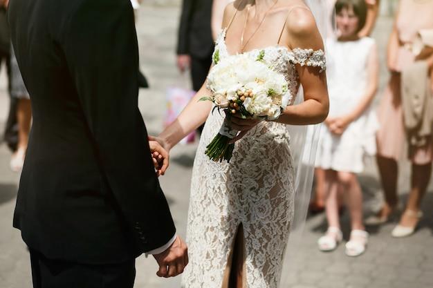 Красивая сексуальная молодая невеста в белом винтажном платье и красивый жених держат друг друга руками