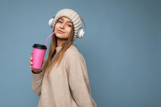 니트 모자 베이지 색 스웨터와 흰색 무선 이어폰을 입고 아름다운 섹시한 성인 금발 여자