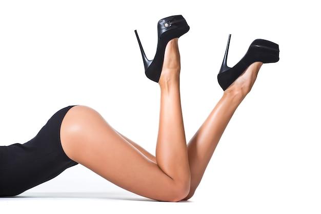 白い孤立した背景にかかととタイツで美しいセクシーで長い女性の脚