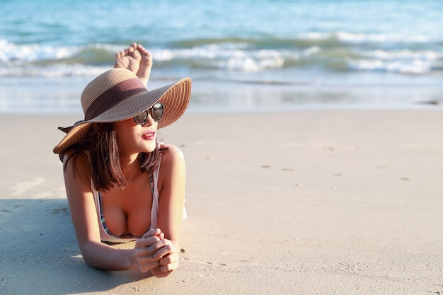 Beautiful and sexy asian girl with hat lying down on the beach