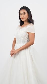 白い背景の上の花嫁のドレスで美しいセクシーなアジアのtanskin女性。