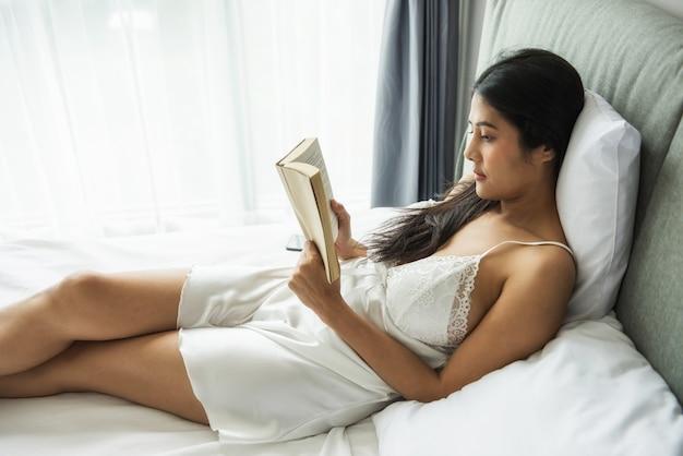 Красивая сексуальная азиатская молодая женщина в белом кружевном нижнем белье нижнего белья читала книгу на кровати с естественным освещением у окна в современной спальне. длинноволосая девушка досуг и хобби в выходные.