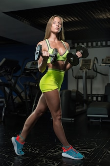 Beautiful sexy athletic muscular young girl. fitness girl trains in the gym, doing exercises with a barbell