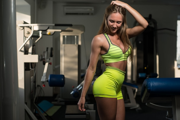 Beautiful sexy athletic muscular young girl girl is posing after a workout