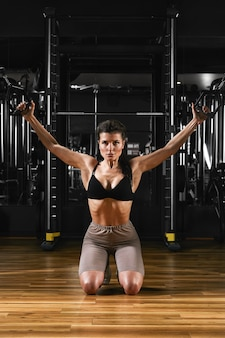 체육관 훈련 가슴에서 밖으로 작동하는 아름 다운 섹시 운동 젊은 백인 여자. 덤벨로 가슴 근육을 펌핑
