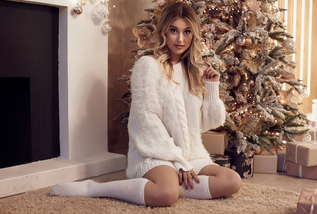 Beautiful sexy blond woman in white sweater smiling near christmas tree