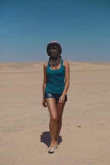 Beautiful sexy blonde girl in helmet and sunglasses wearing in shorts and t-shirt walking across desert.