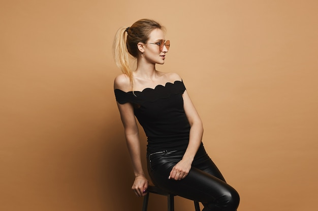 Beautiful and sexy blonde model girl with perfect sporty body and makeup in black leather pants, in black t-shirt and stylish sunglasses sits on stool and and posing at orange wall