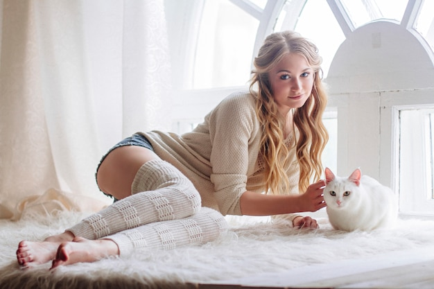Beautiful sexy blonde sitting in window along cat
