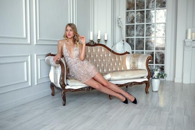 Красивая сексуальная блондинка носить модное золотое короткое платье для вечеринки выходит из места церемонии на диване в интерьере. концепция дорогого курорта и подготовка вечеринки