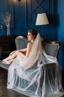 Красивая сексуальная невеста в белом белье, лежа на кровати в своей спальне