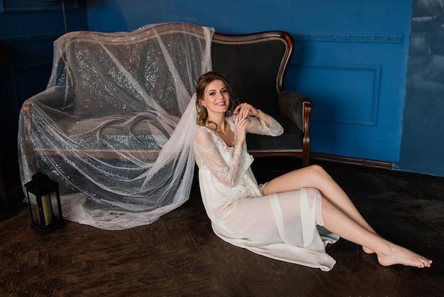 彼女の寝室のベッドに横たわっている白いランジェリーの美しいセクシーな花嫁
