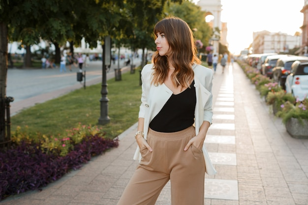 Beautiful sexy  brunette  girl in casual clothes with perfect figure walking around the city center.  elegant style. white jacket.