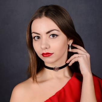Красивая сексуальная брюнетка девушка с красными губами и вьющимися волосами в платье