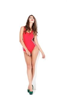 赤い水着と白い壁にハイヒールの美しいセクシーなブルネットの女性