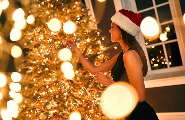 산타 모자와 검은 드레스를 입은 아름다운 섹시한 브루네트 여성은 크리스마스 장난감을 손에 들고 새해 나무를 장식합니다.