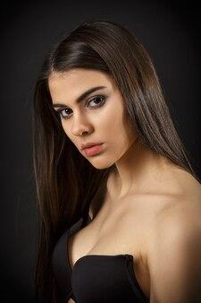 黒のランジェリーでポーズをとる美しいセクシーなブルネットの女性