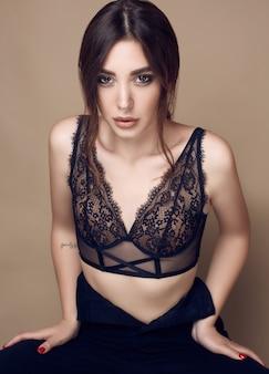 Beautiful sexy brunette woman with juicy lips in dark underwear
