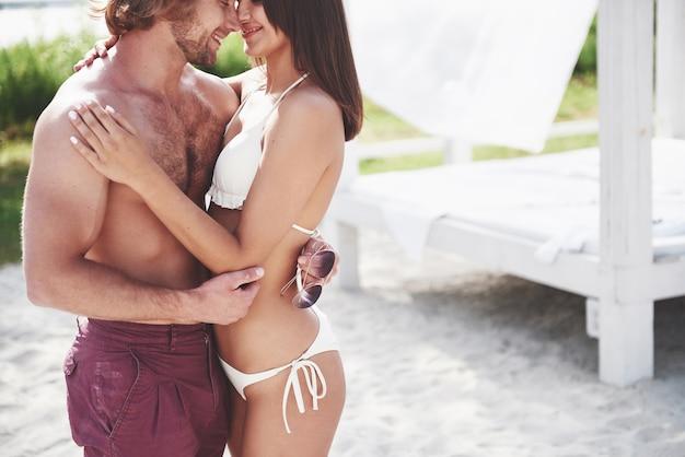 Красивая сексуальная пара парень и девушка в купальниках на пляже. романтично лежащий на песке.