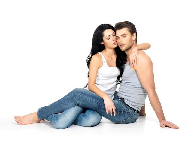 Красивая сексуальная влюбленная пара на белой стене, одетая в синие джинсы и белую майку