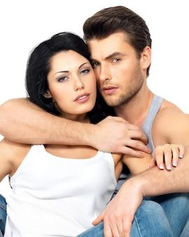 Bella coppia sexy innamorata su bianco vestita di jeans blu e maglietta bianca
